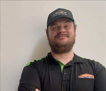 man in black SERVPRO shirt and hat smiling at camera