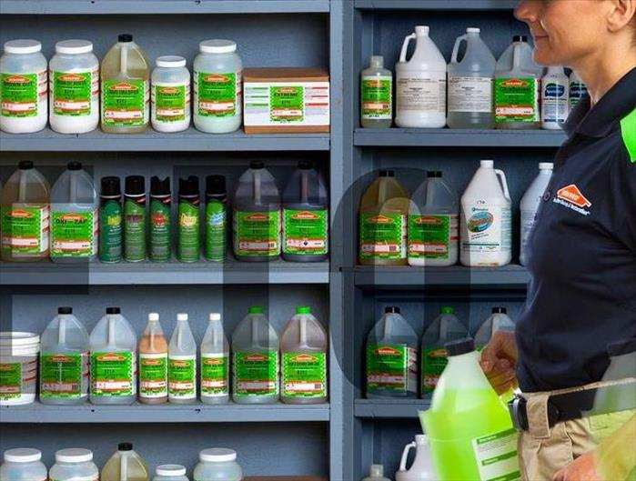 woman in a hat with a ponytail carries a bottle of cleaner in front of shelves filled with cleaning products