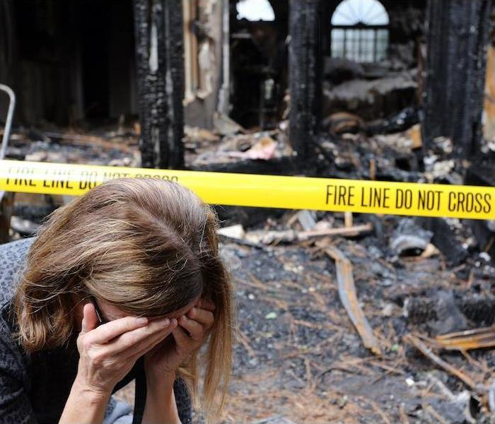 woman with hands covering face upset with burnt house in background