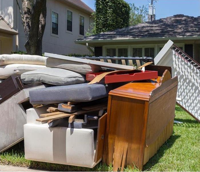 water damaged household furniture sitting outside on front lawn